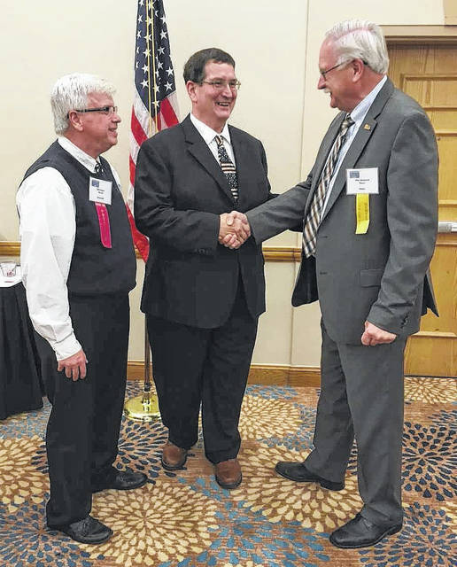 Riverside Mayor Bill Flaute, from left, and Mike Porter, Mount Gilead mayor/president of the Ohio Mayors Association congratulates Sidney Mayor Mike Barhorst on his election as treasurer of the Ohio Mayors Association on June 16.