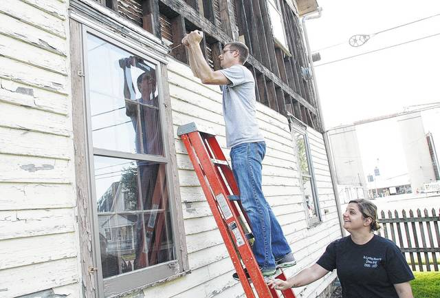 Botkins Historical Society President Greg Geis, left, pulls rotten boards off the side of the historic railroad hotel that is now the society's museum as Vice President Jennifer Duncum, both of Botkins, watches Wednesday, June 14.