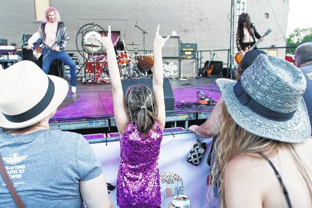 Sarah Patten, center, 8, of Sidney, daughter of Don and Megan Patten, rocks out to ZoSo-The Ultimate Led Zeppelin Experience behind the Historic Sidney Theatre Saturday, June 24. With her were Erica Jo Griffin, left, of Millerstown, and Sarah Thornton, right, of St. Paris. The Worn Flints opened for ZoSo. The concert is the first of a series of big acts which are a collaboration between local organizations Sidney Alive and Raise the Roof for the Arts.