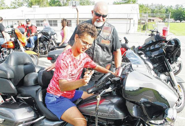 Scott Roddy, right, of Sidney, watches as Camp Dalanda participant Makayla Hoaglin, 14, of Piqua, daughter of Jerry and Betty Hoaglin, tries out Roddy's Harley Davidson motorcycle at Camp Dalanda, Thursday, July 13. Roddy came to Camp Dalanda with the Buckeye Chapter of the Knights of the Inferno, which is an international motorcycle club of former or current firefighters and military members. The Knights of the Inferno stopped by Camp Dalanda to donate a check for $3,000 to Shelby County Arc, which runs Camp Dalanda, an overnight camp in Houston for students in grades 6-10 with developmental disabilities. Shelby County Arc is an agency offering social and recreational programs to those with developmental disabilities in Shelby County.