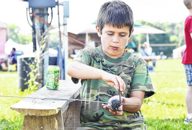 Will Gruters, 9, of Sidney, son of Ryan and Racheal Gruters, makes a slighly darkened S'more at the Holy Angels Parish Picnic, held at Lehman, Saturday, June 24.