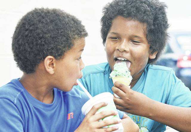 Jace Herron, left, 9, beats the heat with an ice water while Knowledge White, 9, cools down with a mint chocolate chip ice cream cone at Chilly Jilly's Tuesday, July 18. Jace is the son of Melissa Henry, of Sidney. Knowledge is the son of Jay White and Kristina Keith, of Sidney.