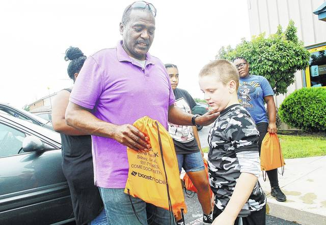 Owner of the Wireless Dock Store Dock Foy, left, hands a free backpack filled with supplies to Dra'gon Elsass, 8, both of Sidney, son of Donald Elsass and Sherry Slife, in front of the Wireless Dock Store Saturday, July 22. Foy was handing out the backpacks until he ran out. The store is locate at 806 West Russell Road.