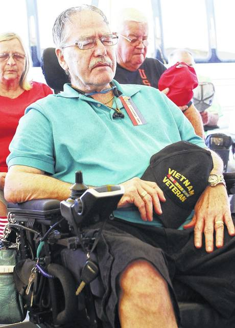 Vietnam Navy veteran Larry Maier, of Anna, closes his eyes as a benediction is said by Duane Mullen during the Shelby County Fair Veterans Program Monday, July 24.
