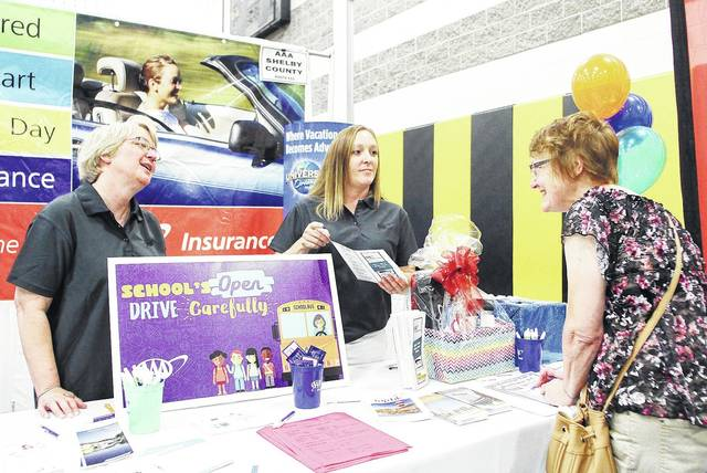 AAA employee Wendy Monnier, left to right, and AAA Insurance Agent Amanda Hayden, talk with Tina Coffield, all of Sidney, as Coffield signs up for the chance to win a gift basket at the Sidney-Shelby County Chamber of Commerce Chamber Expo, Thursday, August 3, at Sidney Middle School.