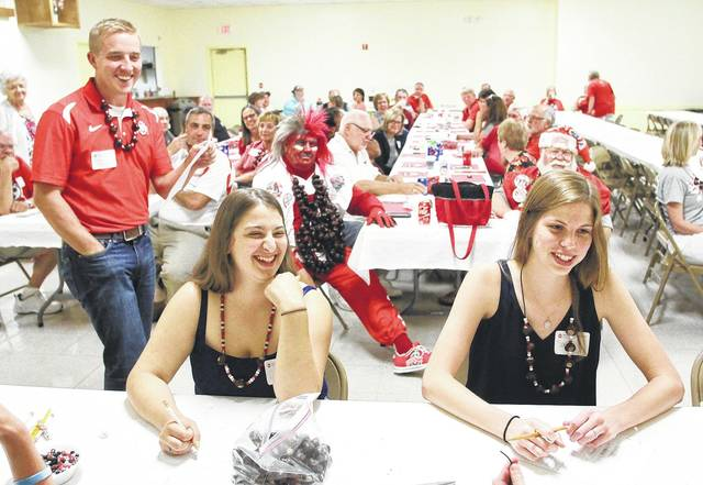 Catie Millhouse, left, front, 18, daughter of Christy and Rich Millhouse, and Sarah Foltz, 18, of Anna, daughter of Gary and Mary Foltz, laugh while taking a OSU trivia quiz given by OSU Alumni Club Member Derek McCracken, far left, all of Anna. The quiz was part of an OSU freshmen event held by the OSU Alumni of Shelby County at the Sidney American Legion Tuesday, Aug. 8. The event brought together 12 Shelby County residents with plans to attend OSU so they could connect with each other and perhaps create a support network in college. The freshmen also made buckeye necklaces and met with Buckeye Man.