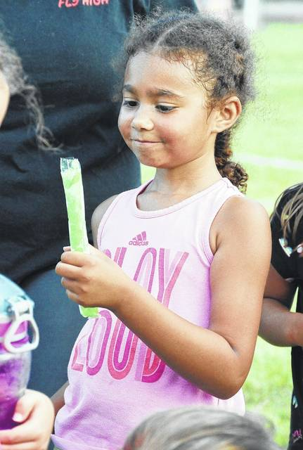 Kallie Steward, 6, of Sidney, daughter of Emily Bauer and Darrick Steward, smiles as she looks at the frozen treat her coach handed out after a Shelby County Youth Soccer practice at Tawawa Park Tuesday, Aug. 15.
