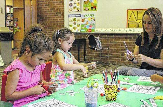 Anna Jenkins, 5, (left), daughter of Rob and Cristina Jenkins of Sidney and Madison Harris, 5, (right), daughter of Warren Harris and Jacqueline Fergus of Sidney, practice their cutting skills with teacher Kelli Lopuch of Sidney, during a lesson in the Sidney-Shelby County YMCA's Kindergarten Readiness Camp.