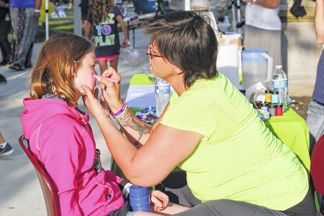 Sadphire Henry, 13, of Sidney, gets a heart painted on her face from Marcy Hauff from American Works during the National Night Out program Tuesday night. She is the daughter of Charles and Neysa Smith.