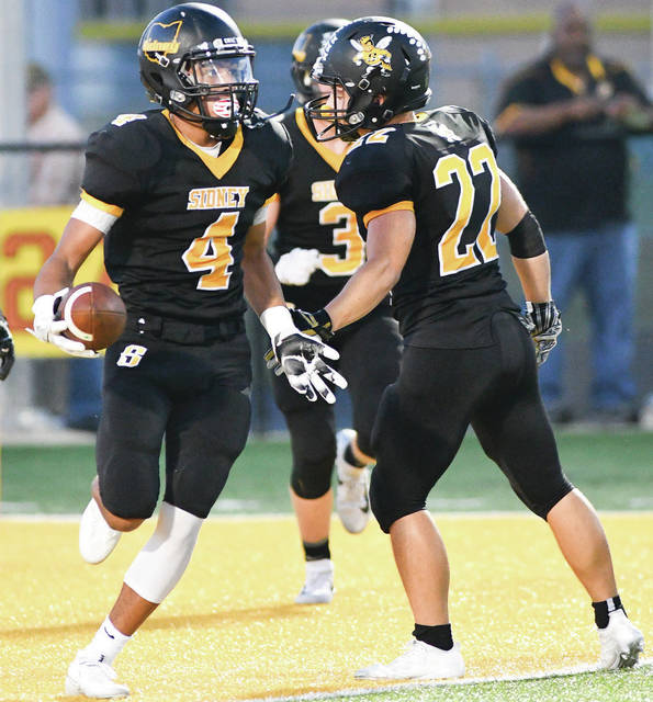 Sidney's Christian Townsend congratulates Darren Taborn after an interception in the first quarter of a Greater Western Ohio Conference game against West Carrollton on Friday at Memorial Stadium.