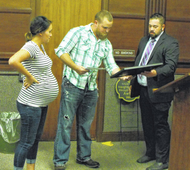 Erica and Ben Ernst receive Sidney's 2017 Neighborhood Beautification Award from Code Enforcement Officer Kirby King at Monday's City Council meeting.