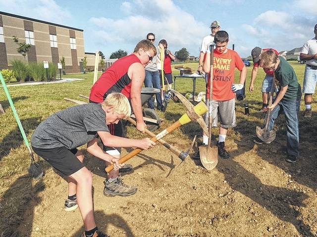 Scouts and family members help Vincent Bajwa dig a trench for a spirit rock at Botkins Local Schools recently. They are, front row left to right, Bajwa's cousin, Mathew Broesch, of Minster, and Boy Scout Troop 14 members Tim Parsons, Brady King and Johnathan Holtzapple, all of Wapakoneta. The spirit rock was a project Bajwa completed to earn his Boy Scout Eagle rank.