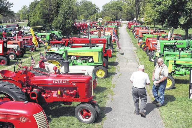 Fall Harvest Festival Staff Coordinator Ed Gigandet, left, of Fort Loramie, and Power Show Coordinator Bob Kohler, of Anna, talk among hundreds of antique tractors at the Fall Harvest Festival at Lake Loramie in 2016.