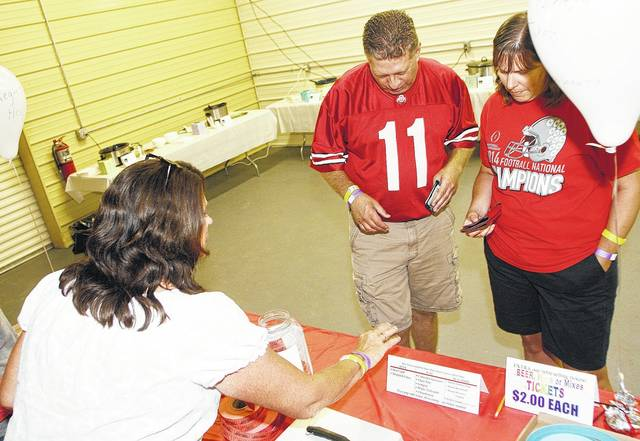 Karen McRill, left, to right, of Anna, talks with Dave and Laura Avdakov both of Englewood at the 4th annual Clear Creek Farm Buckeye Bash and Chili Cook-Off Fundraiser Saturday, Sept. 16. People ate chili and watched Ohio State play at the fundraiser for Clear Creek Farm.
