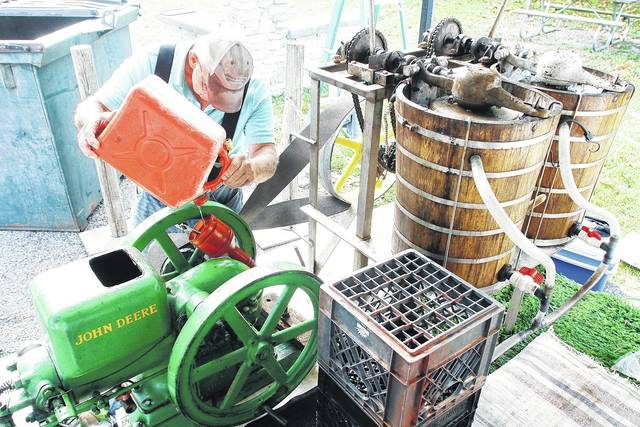 Joe Ginther, of Ottowa, adds gasoline to his 1928 John Deere hit and miss engin that powers his ice cream maker at the 2017 Lake Loramie State park Fall Harvest Festival Sunday, Sept. 17.