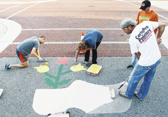 Repainting the roads around Minster with flower filled wooden shoes in preparation for Minster Oktoberfest are, left to right, Greg Zumberger, of Minster, Lora Dues, of New Bremen, Adam Meyer and Kevin Olberding, both of Minster. The group got together early Sunday, Sept. 17 for the painting. Minster Oktoberfest will be held Sept. 29 through Oct. 1.