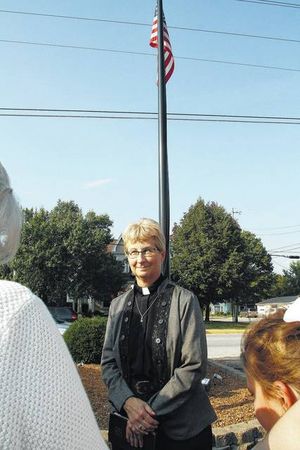 Pastor Charla Grieves, of Botkins, oversees a ceremony Sunday, Sept. 17 for a new flag pole dedicated in memory of Jerry Harrod and all who served. The pole is located next to St. Paul Lutheran Church in Botkins. Harrod served in the Marine Corp..