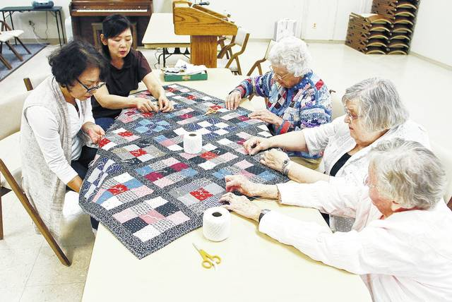 The Ohio Living Dorothy Love Knotters, a quilt club, finish a quilt for hurricane victims, Tuesday, Sept. 19, at Dorothy Love. They are, left to right, Koko Anzawa, of Troy, Miki Motohashi, of Sidney, Margaret Cook, Margaret Boyd and Lois deLorraine, all of Sidney.