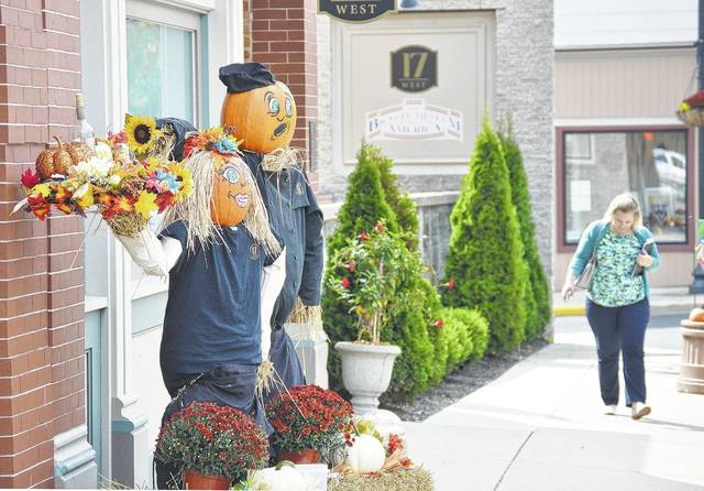 Micayla Gray, of Celina, walks past a pumpkin people display in front of the New Bremen restaurant, 17 West, Wednesday, Sept. 20. The winner of the Village of New Bremen Pumpkin People contest will be announced during Pumpkinfest Saturday, Sept. 23.