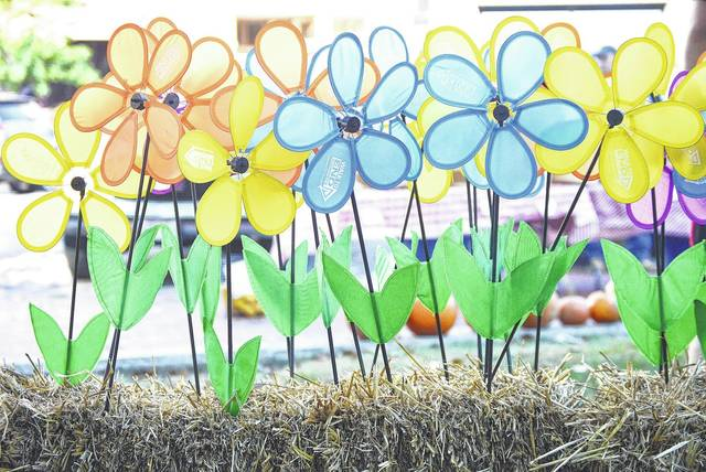 People could pick out the flower color that applied to them before the start of the Sidney-Shelby County Walk to End Alzheimer's on the courtsquare Saturday, Sept. 23. Purple flowers are for people who have lost someone, Orange are for people who support the cause but have not been effected, yellow are for caregivers and blue are for people living with alzheimer's disease.