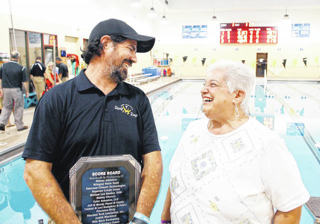 Sidney-Shelby County YMCA Swim Pack President Jeff Payne, left, and longtime Sidney High School and Sidney-Shelby County YMCA swim coach Mary Jannides, both of Sidney, share a laugh after a ceremony celebrating the installation of the new, top of the line, scoreboard hanging on the wall behind them at the Sidney-Shelby County YMCA Monday, Sept. 25. The scoreboard is a huge improvement over the old one which could only show lane times one at a time. The new scoreboard can show the swim times for every swim lane at the same time. The new board is also brighter making it easier to read. A plaque was made recognizing all the donors that made the project possible including the Sidney High School Athletic Department.