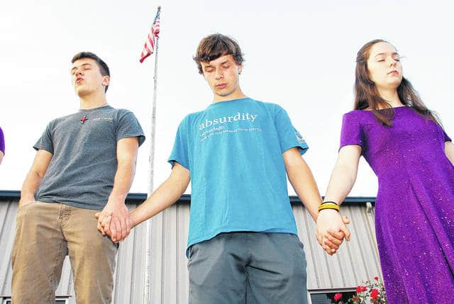 "Praying during a See You at the Pole (SYATP) ceremony at Christian Academy Schools Wednesday, Sept. 27 are, left to right, Noah Joines, 17, son of Maureen and Andrew Joines, Ben Young, 17, son of Tony and Amy Young, and Melody Joines, 15, all of Sidney, daughter of Maureen and Andrew Young. Young's shirt reads, absurdity, using what God has given you to deny God."" The back of Young's shirt had the Bible saying ""The fool hath said in his heart there is no God."" (Psalm 14:1). After saying the Pledge of Allegiance students gathered in a circle and prayed for the U.S. and its leaders both local and federal among other subjects. SYATP is an event where students gather at 7 a.m. around the world at their schools and according to syatp.com pray for their school, friends, families, churches, and communities. Boy Scout Pack 3 raised the flag during the event."