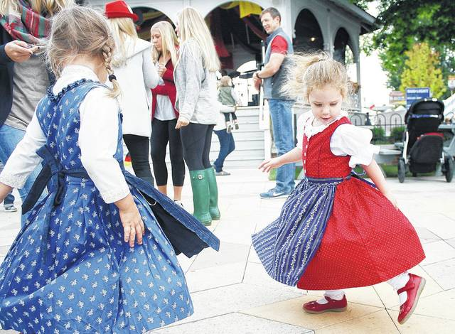 Reese Prenger, left, of Cincinnati, daughter of Brad and Jenna Prenger, dances to polka music with Evie Collins, of Bellbrook, daughter of Amy and Corey Collins, at the 2016 Minster Oktoberfest.