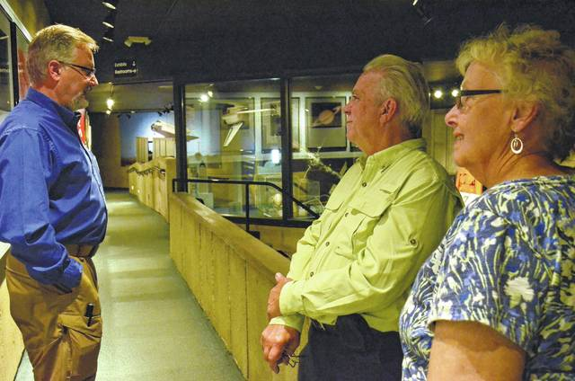 "Greg Brown, left, a volunteer tour guide at the Armstrong Air and Space Museum, answers questions from Keith and Jill Coffey while they tour the museum. Brown has volunteered at the museum for two and a half years. ""This is my happy place,"" he said."