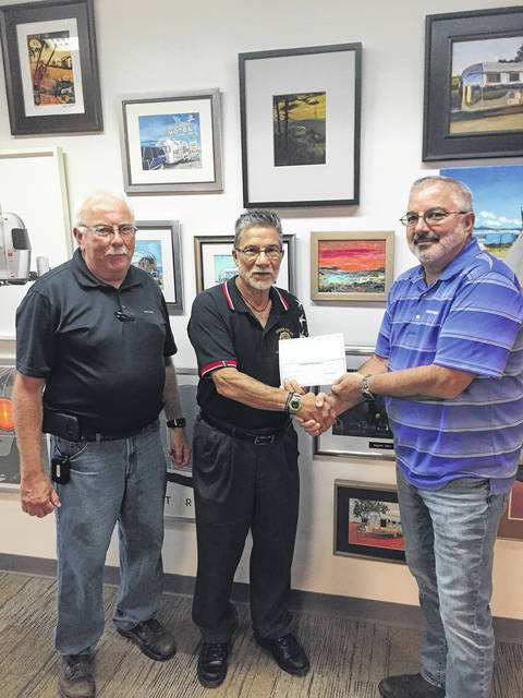 Ron Ludwig, of Airstream, pictured left, and Mark Wahl, senior Vice President of operations with Airstream, pictured right, presented Ron Leininger, adjutant and chaplain with the American Legion Post 493 in Jackson Center, pictured in the center, with a $30,000 check to help meet the post's fundraising goal of $60,000 for a new roof and windows.