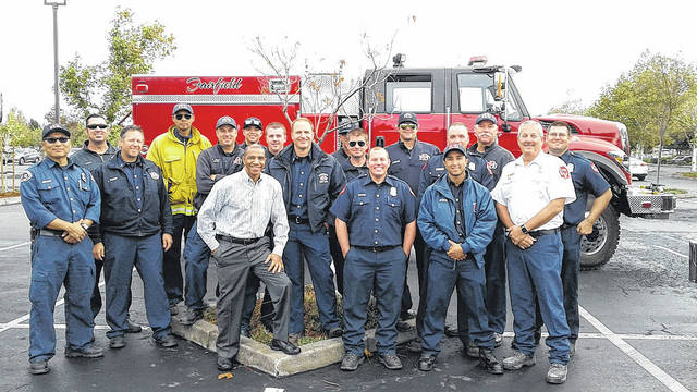 "Former Sidney resident Gregory Stockton-Bolden, of Pleasanton, Calif., front row center in checked shirt, poses in Fairfield, Calif., with Northern California firefighters from the Napa Valley area that was recently devastated by wildfires. Bolden, a former public affairs producer for KNTV/NBC in San Jose, is the son of Bradley Bolden, of Fairfield, Calif., and Sylvia Hudson, of Sidney. Drizzling rains in the Napa Valley area have given the firefighters a much-needed break from tragic fires that have destroyed thousands of acres in Northern California and claimed more than 42 lives. Bolden said, ""It was an honor to stand beside a group of men who are willing to risk their own lives for the sake of others and the preservation of wildlife."""