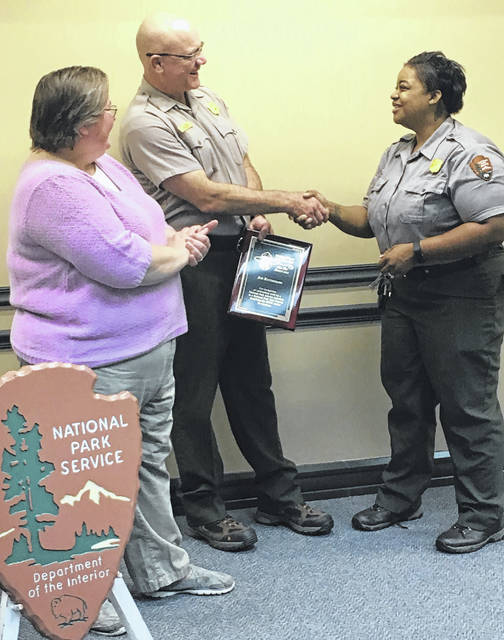 National Park Ranger/Sidney City Council member Joe Ratermann is congratulated by Hopewell Culture National Historical Park Acting Superintendent Jewel Harris, right, as National Parks Travelers Club President Connie Corrigan, left, looks on. Corrigan had just presented Ratermann with the National Parks Travelers Club Flat Hat Award at a ceremony at the Dayton Aviation National Park, Saturday.