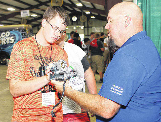 Jackson Center High School student Andrew Brideweser, left, 16, of Jackson Center, son of Chris Brideweser and Tina Brideweser, fits a piece into place on a truck part held by Kirk National Lease recruiter Josh Kolter, of Indianapolis, Ind.. Kirk National Lease is a truck and maintenance and repair company. Watching them is Ryan Bruns, 15, of McCartyville, son of Ron and Margie Bruns. The hands-on-program was held in September at the Shelby County Fairgrounds.