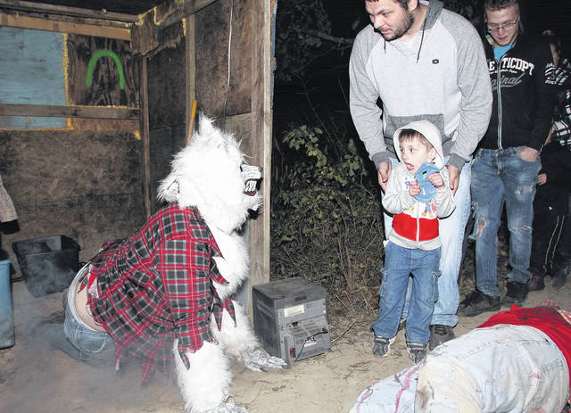 Dressed as a werewolf Matt Hatfield, left to right, of Sidney, jumps out at a terrified Jayden Grimm, 4, followed by his father Ricky Grimm, both of Fort Loramie, Saturday, Sept. 30. Werewolves are just part of the sprawling Sidney Haunted Woods. A portion of the event's proceeds will go to local cancer patients. Jayden is also the son of Crystal Yantis.