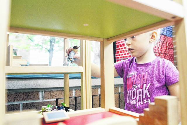 Julie Swenger, 3, of New Bremen, daughter of Natasha and Steve Dwenger, plays with a doll house at the New Bremen Public Library, Tuesday, Oct. 10.