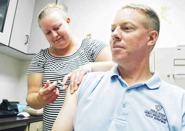 Public Health Registered Nurse Alicia Cooper, left, of Jackson Center, administers a flu vaccination to Rusty Schwepe, of Sidney, at the Sidney-Shelby County Health Department, Wednesday, Oct. 11.