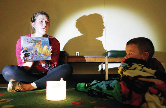 Rebecca Gehret, left, of Anna, prepares to read a scary story to Spencer Kuenning, right, of Minster, son of Andy and Lindsey Kuenning, and other children, at the New Bremen Public Library during Family Night Tent - In Thursday, Oct. 12.
