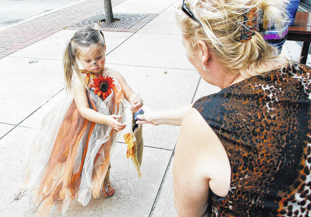 Annie Loraine-Bruns, left, 3, daughter of Heidi Loraine-Bruns, gets some candy from Berkshire Hathaway agent Sandi Shipman, both of Sidney. Annie was Trick or treating during the Downtown Fall Festival, Saturday, Oct. 14.