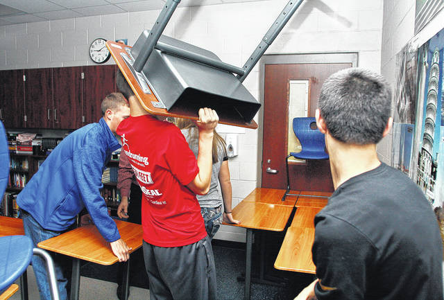 Using desks and chairs to barricade the door of their Fairlawn High School Social Studies room are tenth grade students, left to right, Cade Allison, 15, of Maplewood, son of Dean and Cari Allison, Isaac Ambos, 16, son of Matt and Sara Ambos, and Garrett Smail, 15, both of Sidney, son of Kreig and Debbie Smail. Fairlawn Local School students practiced their lockdown drill Tuesday, Oct. 24. The students would use what they learned from the drill in the event of a school intruder. Representatives from the Shelby County Sheriff's Office were going from class to class before and after the drill to talk to kids about what to do in the case of a school shooter. The Sheriff's Office representatives were also evaluating safety procedures at the school. Classrooms come equipped with Bolo Sticks which are placed at the base of each door as an additional lock. The lights are turned off and the kids squeeze into a corner of the room not visible from the door.