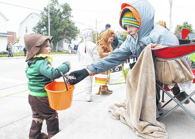 Howell Sullivan, left, 2, gets some candy from Isaac Koenig, 2, both of Botkins, during Trick-or-Treat in Botkins Sunday, Oct. 29. In the background are Howell's brothers Bennett Howell, second from left, 6, and Anderson, 5, both of Botkins. The Howell brothers are the children of Luke and Dana Howell. Isaac is the son of Cindy and Alex Koenig. Trick or treat will be held in Sidney, Port Jefferson and Tawawa Tuesday from 6 to 7:30 p.m.