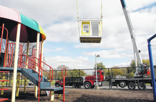 """A new playhouse flies through the air and into the fenced in Sidney-Shelby County YMCA playground Tuesday, Oct. 31. The playhouse was built by area students under the guidance of Ferguson Construction during the recent 2017 Career Exploration Academy put on by Workforce Partnership of Shelby County and the Shelby County United Way. Ferguson Construction provided the material and tools for the playhouse's construction. Sidney High School students Dylan Shoukri and Malcom Barnes were on hand during the delivery to make some last minute additions to the playhouse. The two students had also helped paint the playhouse in their Workforce Tech class. A group of excited YMCA kids got the honor of being the first to enter the playhouse after it was in place. One of the first kids, Clayton Smith, 2, son of Jason and Andrea Smith, to enter said of the playhouse arriving, """"This is the most awesomest day ever."""""""
