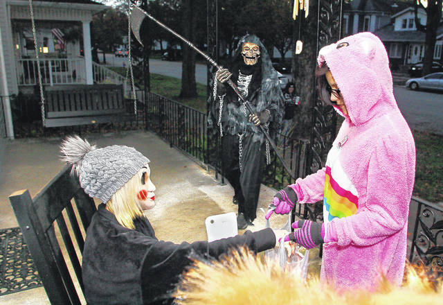 Jodi New, left, puts candy in the bag of Alexis Rivera, 12, daughter of Trish Graham, dressed as Cheer Bear, as Larry Panning approaches dressed as Death during Halloween night in Sidney. All are from Sidney.