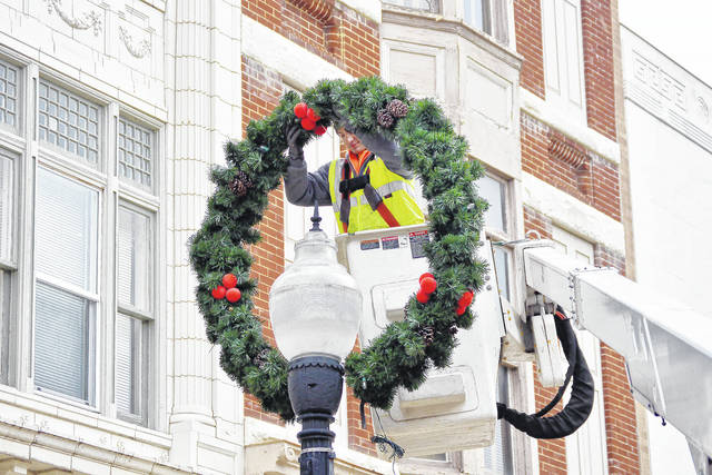 City of Sidney employee Ryan Mullen II, of Sidney, puts up a giant wreath on a street lamp on Poplar Street Tuesday, Oct. 31. Mullen spent Halloween morning putting Christmas wreaths on most of the street lamps around the courtsquare area.