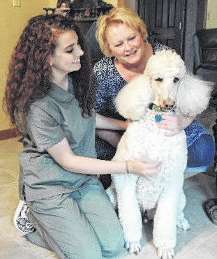 Aria Gibson, left, a senior at Minster High School, helps Sandra White care for Jackson, a 15-year-old standard poodle. White owns Xtra Mile Pet Services that tends to family animals in their own homes when owners travel out of town.