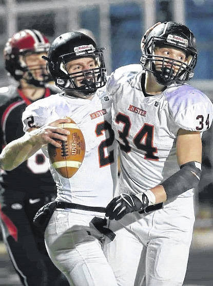 Minster senior quarterback Jared Huelsman, left, celebrates a touchdown run with August Boehnlein, right, during a state semifinal against Norwalk St. Paul last Friday.