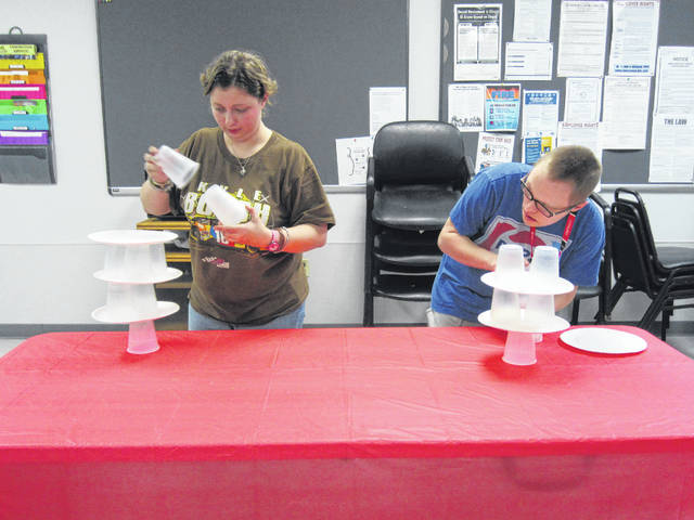 "Ashley Weber, left, of Sidney, and Jesse McName, of Botkins, race to stack cups and paper plates during a Friday Night Out titled ""Ridiculous Game Night."""