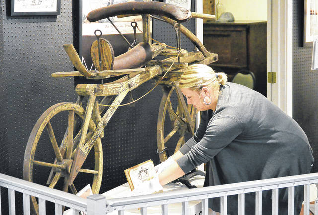 """Then Bicycle Museum of America intern Lindsey Pape, of New Bremen, adjusts a descriptive sign next to the world's first bicycle, in June. The bike will be featured in an episode of the Travel Channel's """"Mysteries at the Museum,"""" Thursday, Nov. 16."""