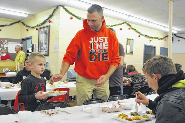 Justin Neu, center, of Sidney, helps his son J.T., left, serve a meal during the Alpha Community Center's Thanksgiving dinner on Friday. The Alpha Center has served a Thanksgiving meal annually for 22 years according to director Jan Geuy. Hundreds of people ate the Center on Friday. Dinner included turkey, ham, mashed potatoes, dressing, macaroni and cheese, green bean casserole and pies donated by The Spot.