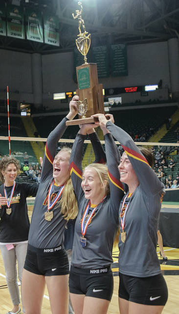 New Bremen seniors Paige Jones, left, Tara Springer, middle, and Julia Goettemoeller, right, hoist the Division IV state championship trophy following the Cardinals' 3-0 win over St. Thomas Aquinas on Saturday at Wright State's Nutter Center.