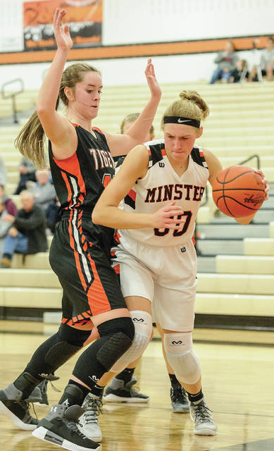 Minster's Courtney Pregner, right, dribbles with pressure from Jackson Center's Olivia Clark during a nonconference game on Saturday at Minster.
