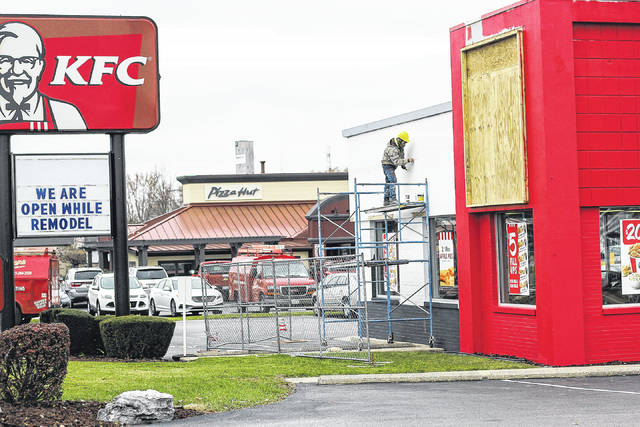 Bobby Galindo, of Delta Construction from Indianapolis, Ind., works on a wall of the KFC restaurant in Sidney, Thursday, Nov. 16.